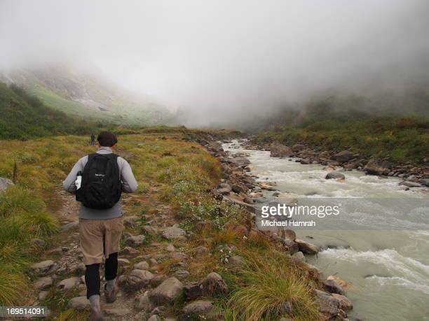 Lone trekker walk amongst misty clouds while hiking into the Annapurna Sanctuary in Nepal. The Annapurna Sanctuary is one of the most popular treks...