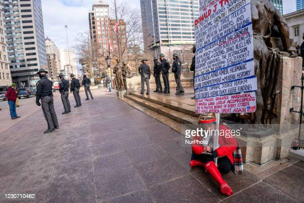 Lone Trump supporter checks her phone while holding a sign outside the Ohio Statehouse after President Joe Biden was sworn into office in the wake of...