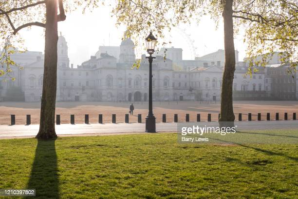 Lone walker crossing Horse Guards Parade from St James's Park on 16th April 2020 in London, United Kingdom. Normally crowded with people London is...
