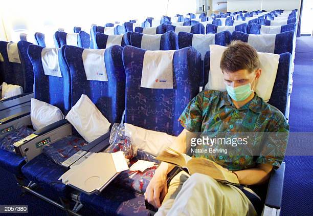 Lone western visitor wearing a surgical mask reads a book in a nearly empty Air China flight from Hong Kong to Beijing on June 5, 2003 in Beijing,...