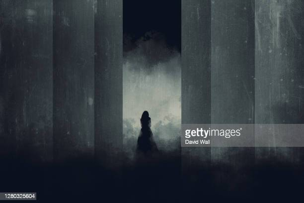 a lone woman in a dress. silhouetted in a dark corridor. with a glowing light behind. - column stock pictures, royalty-free photos & images
