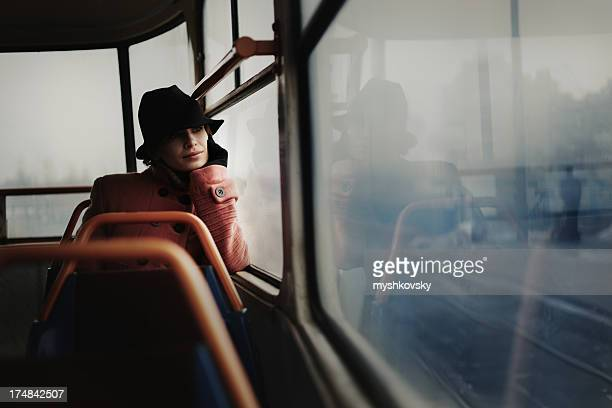 Lone woman in a train car looking off into the distance