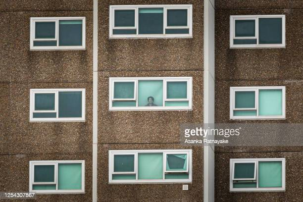 Lone woman is seen looking out the window of her apartment at the North Melbourne Public housing flats on July 05, 2020 in Melbourne, Australia. Nine...