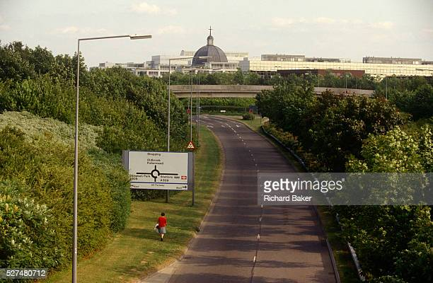 A lone woman pedestrian has to walk along a grass verge to enter the outer limits of Milton Keynes