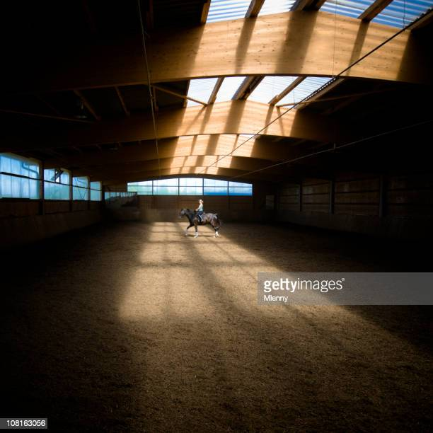 Lone Woman Riding Horse in Indoor Ring