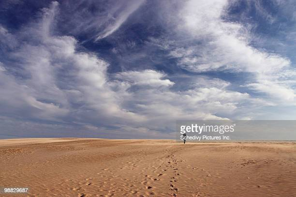 lone woman walking on sand dune under blue sky. - kitty hawk north carolina stock pictures, royalty-free photos & images