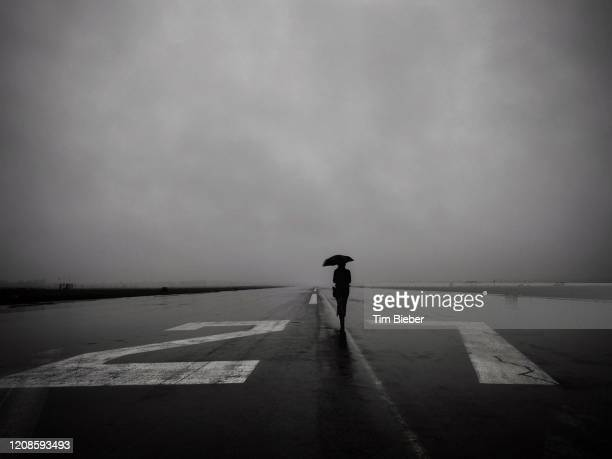 lone woman with umbrella on empty runway 27 left at tempelhof airport in berlin on a rainy day. - estremismo foto e immagini stock