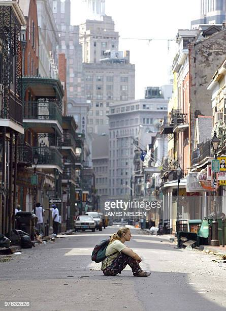 A lone women sits in the middle of Bourbon Street in the French Quarter of New Orleans Louisiana 31 August 2005 in aftermath of Hurricane Katrina...