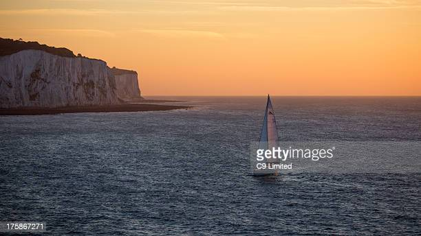 CONTENT] A lone yacht sails past the white cliffs of Dover at dawn Clear skies and the early morning sun lighting the scene