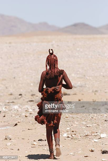 Lone young Himba woman walking in desert, Namibia