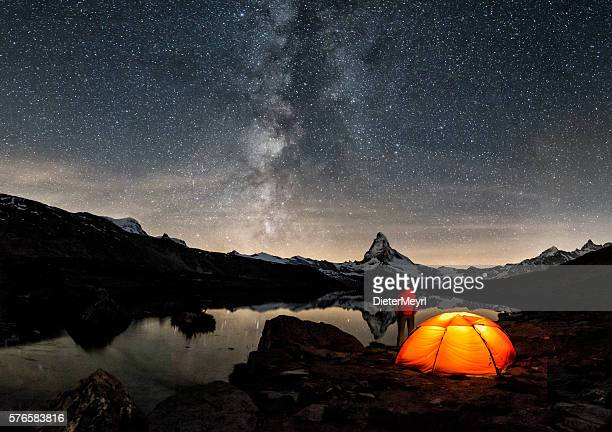 loneley camper under milky way at matterhorn - camping stock photos and pictures