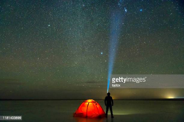 loneley camper under milky way  on the ice - geminid meteor shower stock pictures, royalty-free photos & images