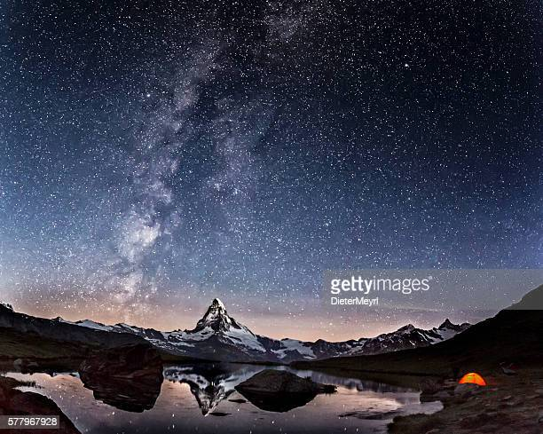 loneley tent under milky way at matterhorn - milky way stock pictures, royalty-free photos & images