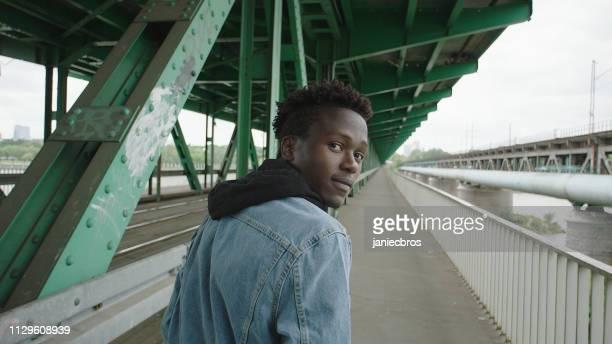 jeune homme de solitude marchant sous le pont. regarder loin - tourner photos et images de collection