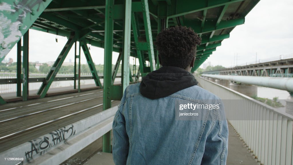 Loneliness young man walking under bridge. Looking back : Stock Photo
