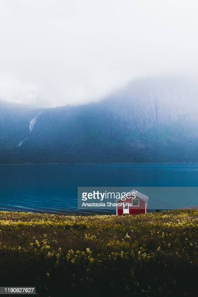 lonely abandoned red house on the meadow with view of the mountains and waterfall in norway - nordic countries stock pictures, royalty-free photos & images