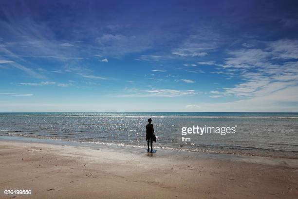 Lonely and unrecognizable woman is standing on the beach and looking at the horizon