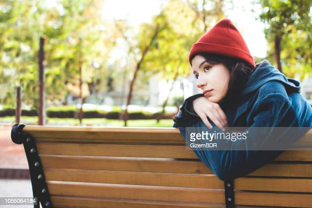 lonely beautiful woman is sitting on the bench - brown hat stock pictures, royalty-free photos & images