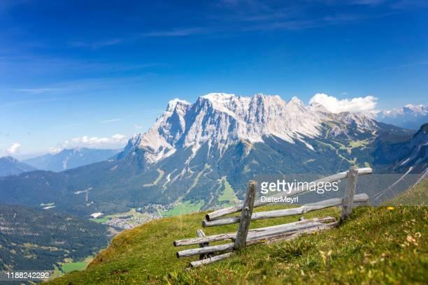 einsame bank mit blick auf zugspitze, alpen - oberbayern stock-fotos und bilder