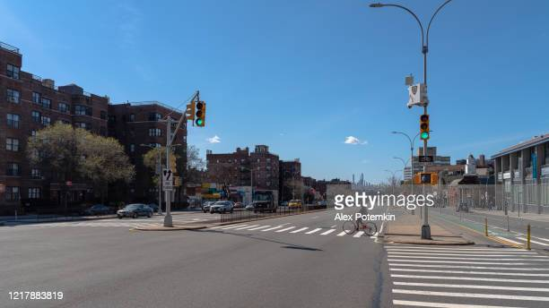 lonely bicyclist crossing the empty queens boulevard deserted because of the covid-19 outbreak. - alex potemkin coronavirus stock pictures, royalty-free photos & images