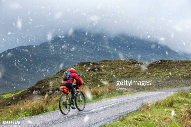 Lonely biker cycling through the Scottish Highlands on heavily laden touring bicycle along single track road during sleet in spring Scotland United...
