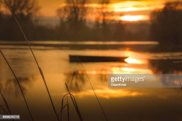 半分凍った川に冬の日没で孤独なボート