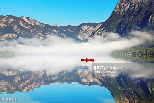 Lonely boat on Lake Bohinj in Slovenia on a foggy morning