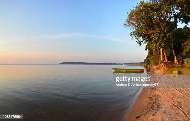 lonely boat on still water in kalangala - uganda stock pictures, royalty-free photos & images