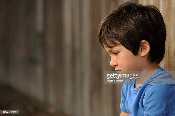 Lonely boy in a blue shirt sits against a wooden fence