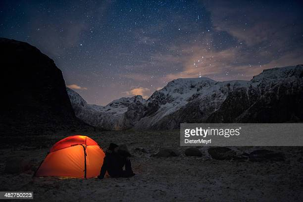 Lonely camper looking at the starry sky in wintertime