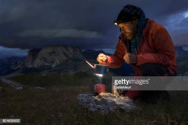 Lonely camper with gas cooker in Alps