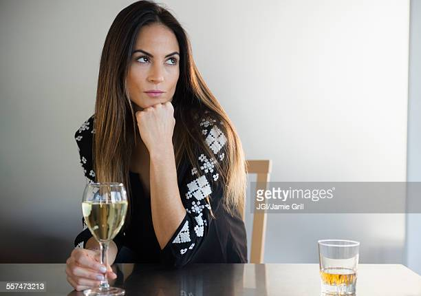 Lonely Caucasian woman drinking white wine in bar