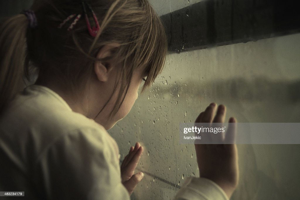 Lonely child looking through window : Stock Photo