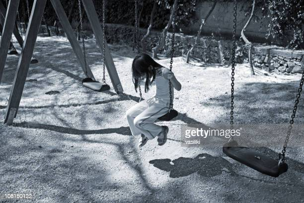 A lonely child on a swing set by herself