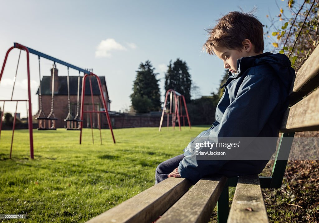 Lonely child sitting on play park playground bench : Stock Photo