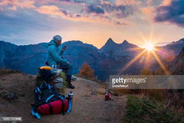 einsame kletterer genießt kaffee bei sonnenaufgang - alpen - überleben stock-fotos und bilder