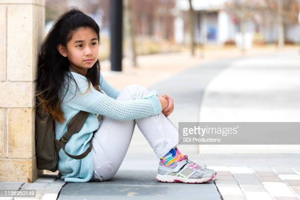 lonely elementary schoolgirl waits for ride after school. - school girl shoes stock pictures, royalty-free photos & images