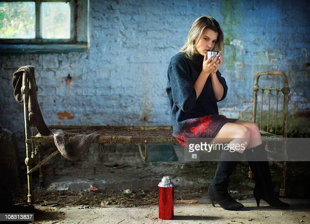 lonely girl sits in an old house and drink tea. - hot dirty girl stock photos and pictures