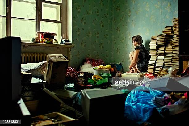 lonely girl sitting in a room littered with things - messy stock pictures, royalty-free photos & images