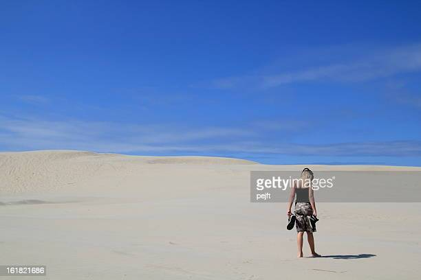 Lonely girl walking in sand dunes / desert