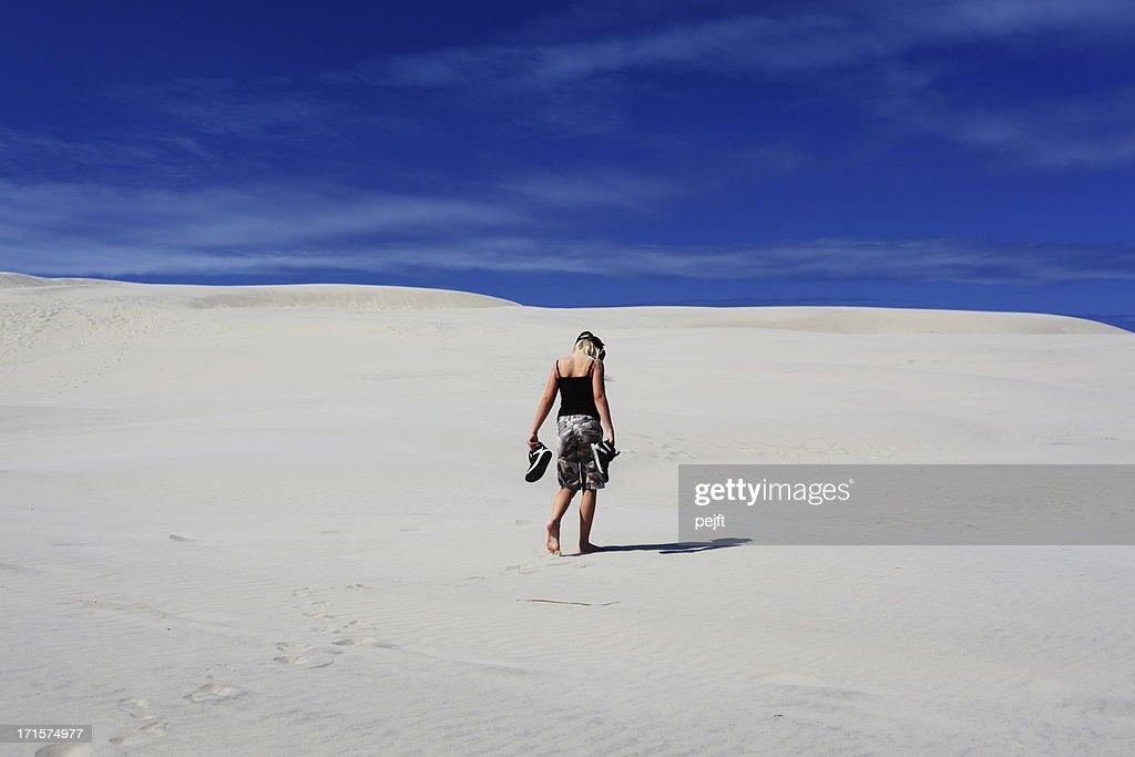 Lonely girl walking in sand dunes / desert : Stock Photo