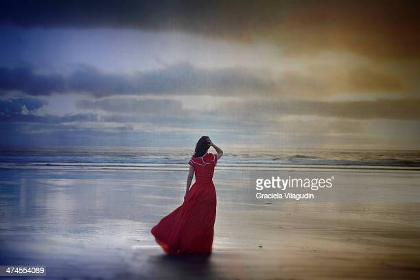 lonely girl with red vintage dress at the beach - long dress stock pictures, royalty-free photos & images
