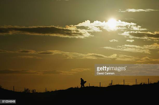 A lonely golfer walks from the 7th tee in the evening light at Royal Birkdale Golf Club on April 21 2004 in Birkdale England