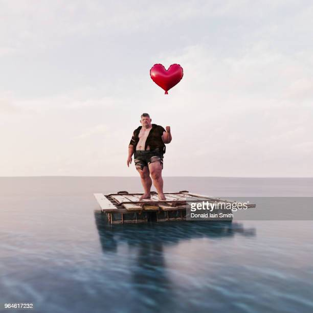 Lonely heart man holding heart shaped balloon standing on raft in calm ocean