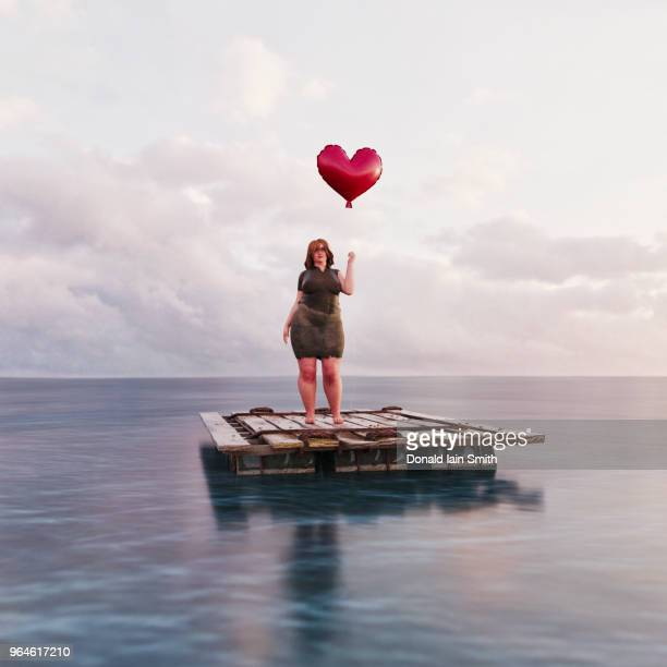 lonely heart woman holding heart shaped balloon standing on raft in calm ocean - ugly fat woman stock photos and pictures