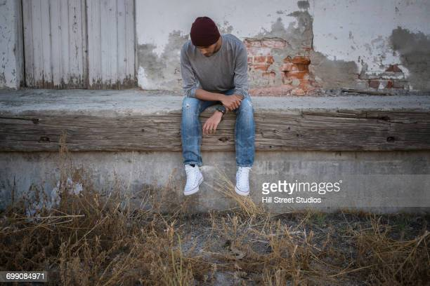 lonely hispanic man sitting on urban wall - tensed idaho stock photos and pictures
