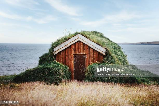lonely isolated small house with grass rooftop and ocean on background - shack stock pictures, royalty-free photos & images
