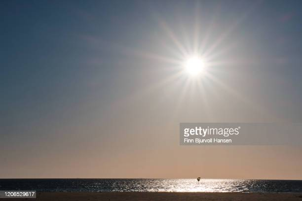 lonely kitesurfer on a foilboard in the atlantic ocean at sunset - finn bjurvoll stock pictures, royalty-free photos & images