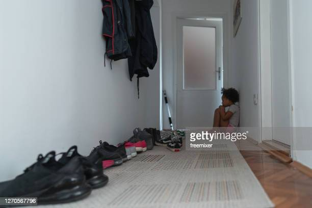 lonely little girl sitting on floor in apartment corridor - black shoe stock pictures, royalty-free photos & images