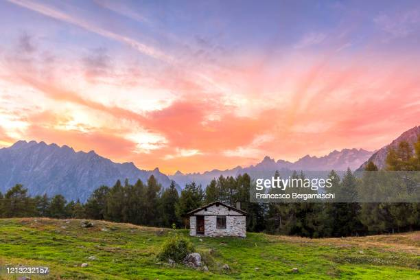 lonely log cabin in the mountain with sunset clouds. - italia ストックフォトと画像